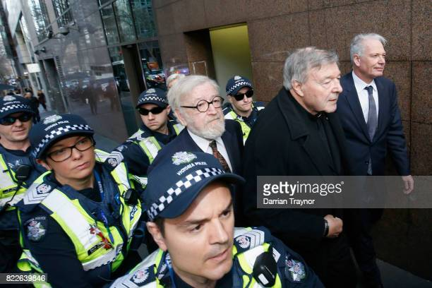 Cardinal Pell walks with a heavy police guard to the Melbourne Magistrates' Court on July 26 2017 in Melbourne Australia Cardinal Pell was charged on...