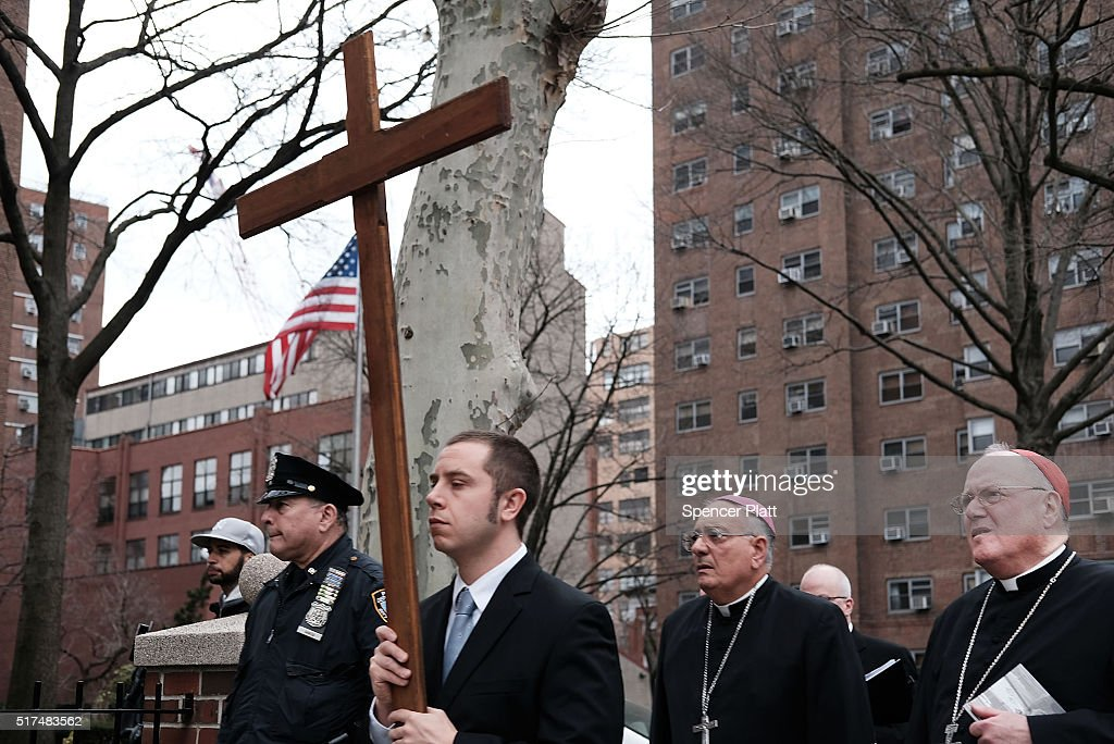 Cardinal Timothy Dolan archbishop of New York City joins worshippers during the Way of the Cross procession over the Brooklyn Bridge on March 25 2016...