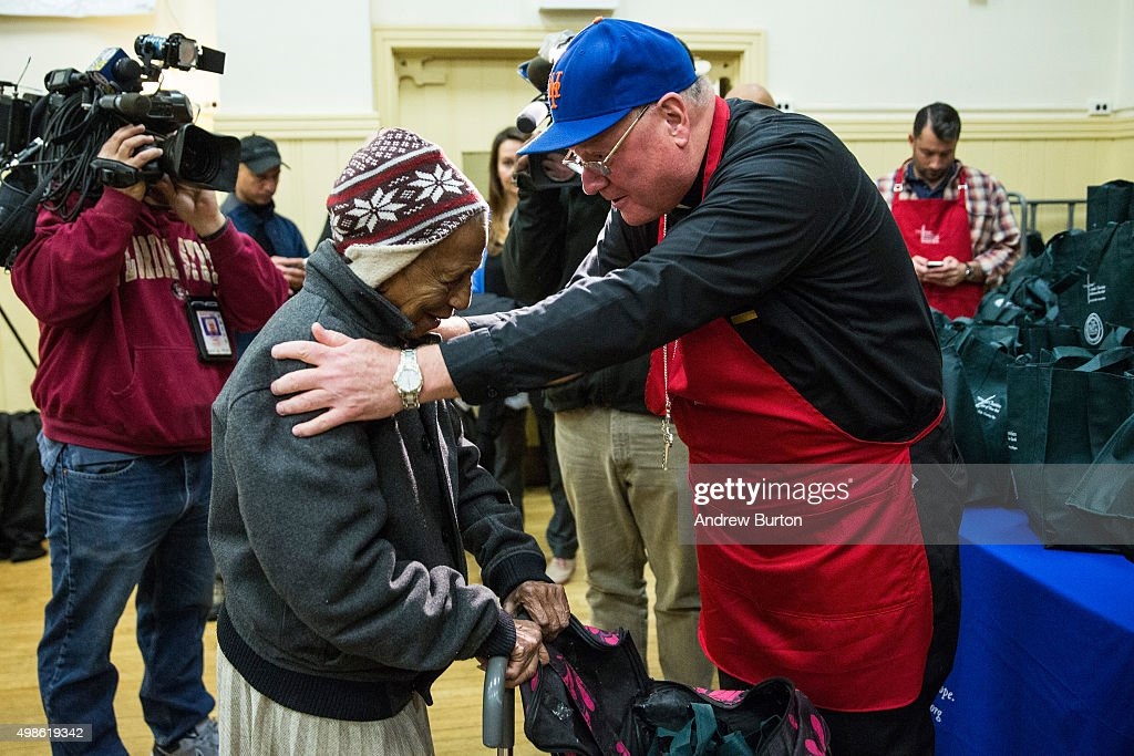 Cardinal Timothy Dolan Archbishop of New York for the Roman Catholic Church helps hand out food for Thanksgiving meals to those in need at the Lt...