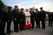 Cardinal Timothy Dolan pauses for a photo with police before entering an interfaith prayer service at Mount Sinai United Christian Church to mark the...