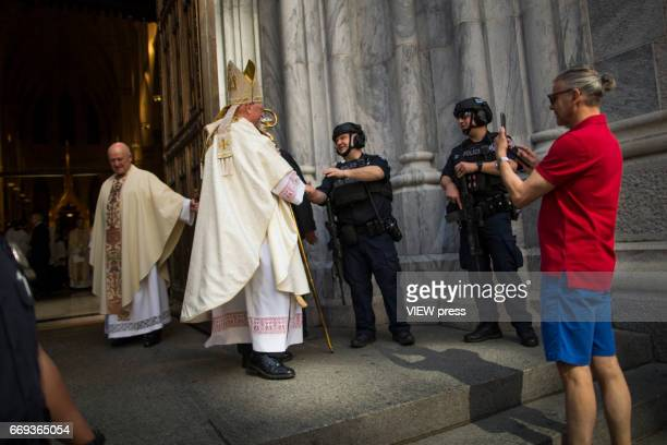 Cardinal Timothy Dolan shakes hands with NYPD officers as he arrives to St Patrick'u2019s Cathedral for mass while people take part in the Annual...