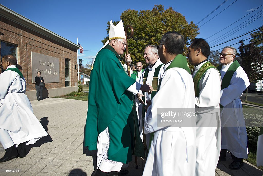 Cardinal Timothy Dolan shakes hands with priests during a procession for a Mass of Remembrance marking the first anniversary of Hurricane Sandy at Our Lady Star of the Sea church on October 27, 2013 in Staten Island borough of New York City. Hurricane Sandy made landfall on October 29, 2012 near Brigantine, New Jersey and affected 24 states from Florida to Maine and cost the country an estimated $65 billion.