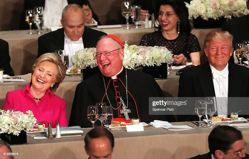 Cardinal Timothy Dolan sits between, Hillary Clinton and Donald Trump attend the annual Alfred E. Smith Memorial Foundation Dinner at the Waldorf Astoria on October 20, 2016 in New York City.The white-tie dinner, which benefits Catholic charities and celebrates former Governor of New York Al Smith, has been attended by presidential candidates since 1960 and gives the candidates an opportunity to poke fun at themselves and each other.