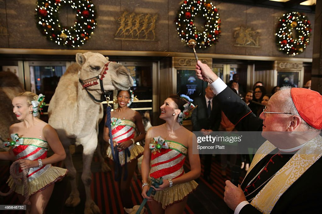 Cardinal Timothy Dolan stands with members of the Rockettes as he blesses camels and other animals at the start of rehearsals for 'Living Nativity' in the 2015 Radio City Christmas Spectacular on November 5, 2015 in New York City. Camels, sheep and a pony were included in the early morning procession to the front of Radio City Music Hall where the animals were greeted by members of the Rockettes.The 'Living Nativity' scene has been part of the production since the Christmas Spectacular's inception in 1933.