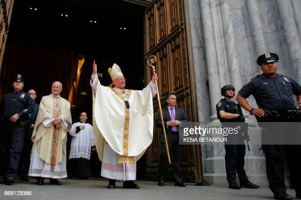 Cardinal Timothy Dolan waves as he leaves St Patrick's Cathedral during the annual Easter Parade and Easter Bonnet Festival on the Fith avenue April...