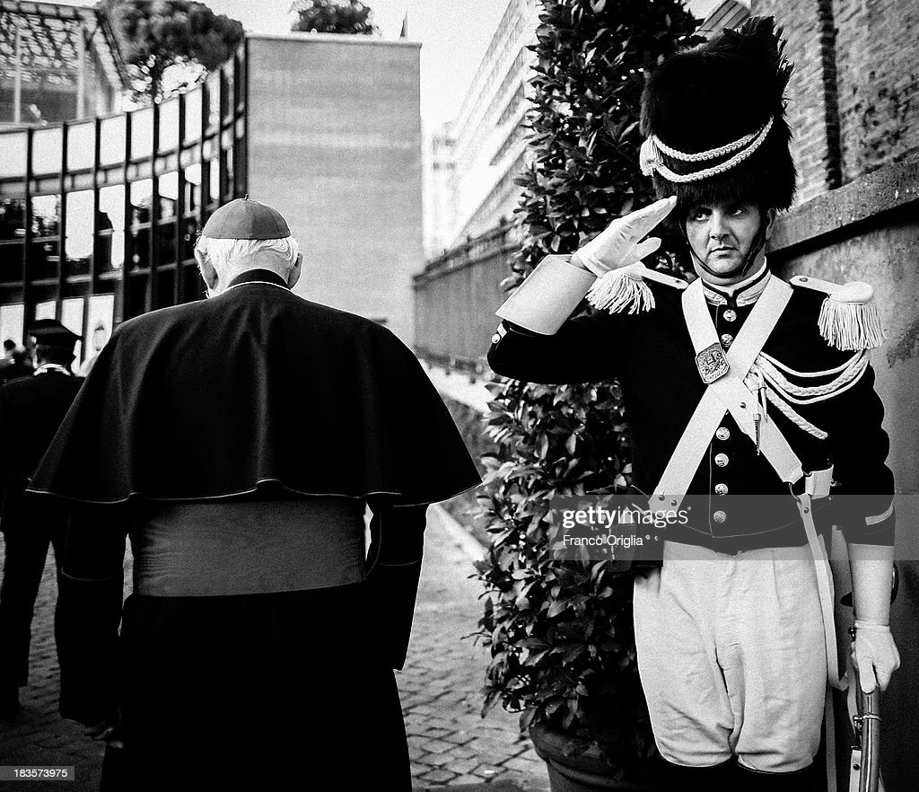 A Cardinal walks past a Vatican Gendarme as they attend the celebration of San Michele Arcangelo patron Saint of Gendarmerie Corps of Vatican at the gardens of the Vatican Museums on September 26, 2013 in Vatican City, Vatican. After the success of his Social networking accounts of Twitter and Facebook, Pope Francis joined Instagram, reporting today more than 8000 followers.