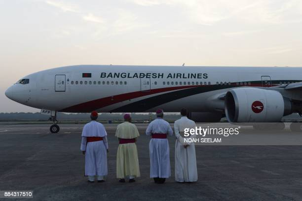 Cardinals stand on the tarmac as a Bangladesh airlines aircraft carrying Pope Francis prepare for departure at the airport in Dhaka on December 2...
