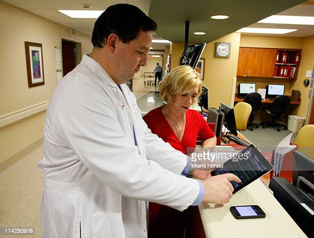 Cardiologist Dr Jose Soler demonstrates to hospital CEO Dianne Goldenberg an app on an iPad to review medical tests of one of his patients at...
