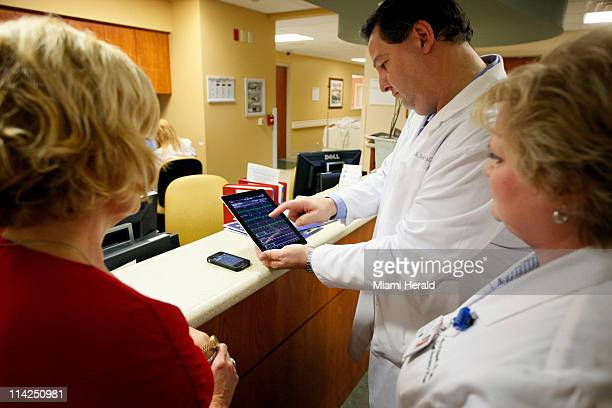 Cardiologist Dr Jose Soler demonstrates to hospital CEO Dianne Goldenberg let and CNO Cathy Philpoh an app on an iPad to review medical tests of one...