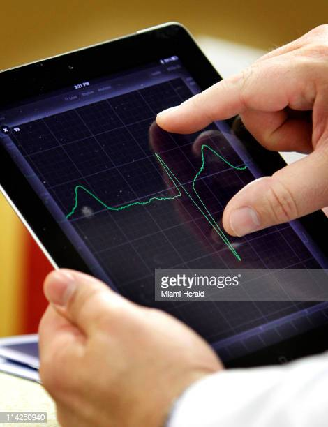 Cardiologist Dr Jose Soler uses an app on an iPad to review medical tests of one of his patients at Northwest Medical Center in Margate Florida on...