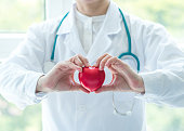 Cardiovascular disease doctor or cardiologist holding red heart in clinic or hospital exam room office for professional medical and cardiology health care service and world heart health day concept