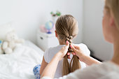 Female plaiting her daughter long hair