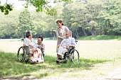 A helper to support with a wheelchair senior.