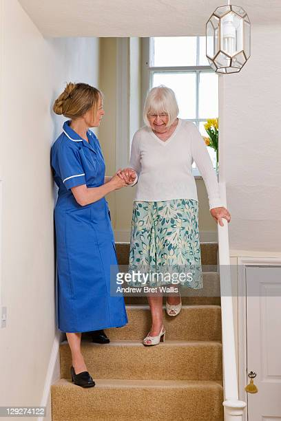 care worker helps an elderly woman down the stairs