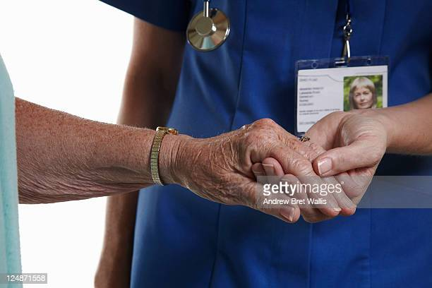 Care worker holds an elderly woman's hand