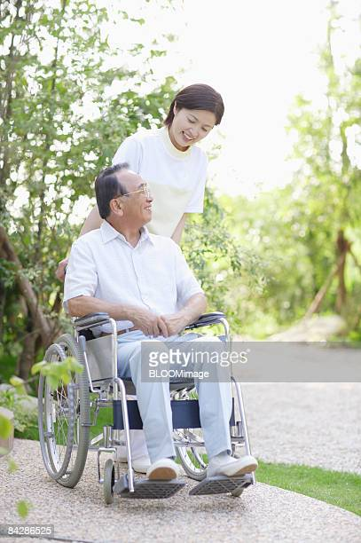 Care worker talking with senior man in wheelchair