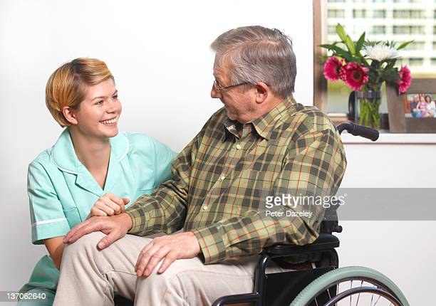 Care worker with senior citizen in care home