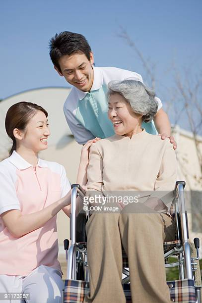 Care workers talking with senior woman in wheelchair