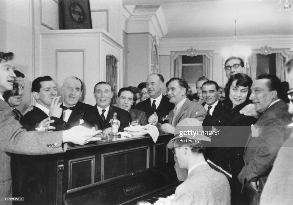 Career criminals and journalists at a party at Gennaro's restaurant in Soho, London, given by British gangster Billy Hill to launch his autobiography 'Boss of Britain's Underworld', December 1955. Left to right: Soho Ted, Bugsy, Groin Frankie, Billy Hill, Ruby Sparkes, Frankie Fraser, College Harry, Frany The Spaniel, Cherry Bill, Johnny Ricco, a female journalist, Russian Ted and a publisher. A journalist is at the piano. Original publication: Picture Post - 8180 - That Ex-Gangster Party - pub. 3rd December 1953