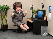 Baby sitting in a business cubicle wearing a business dress with an expression of panic on her face