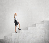 Young businesswoman going up a a concrete stairs steadily along a concrete wall. Concept of career growth.