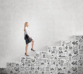 Young businesswoman going steadily up a a concrete stairs with drawn business icons on it along a concrete wall. Concept of career growth.