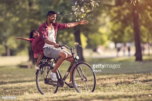 Sorglose afroamerikanischen Vater und Tochter Fahrradfahren im park.