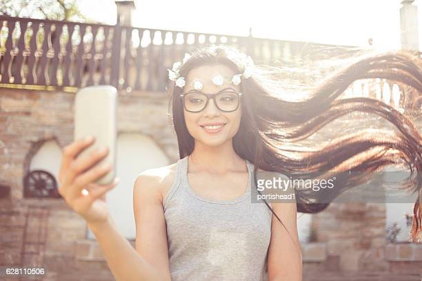 Carefree boho woman making selfie outdoors