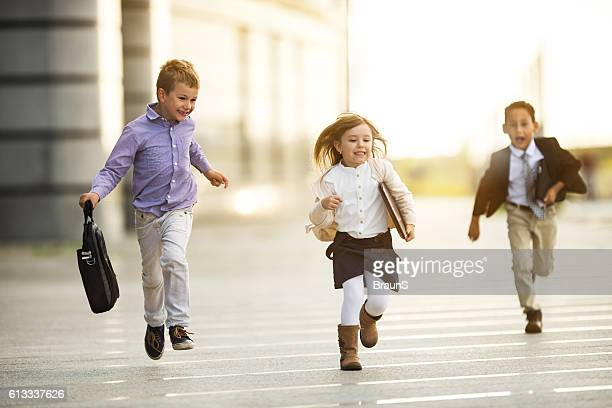 Carefree business kids having fun while running outdoors.