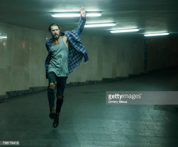 Carefree Caucasian man skipping in tunnel