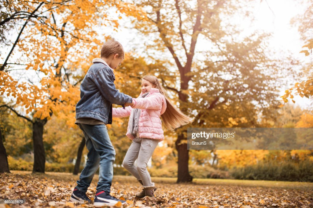 Carefree children holding hands and spinning in the park. : Stock Photo