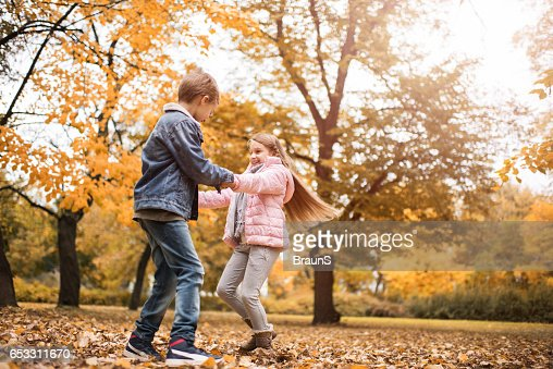 Carefree children holding hands and spinning in the park. : Stock-Foto
