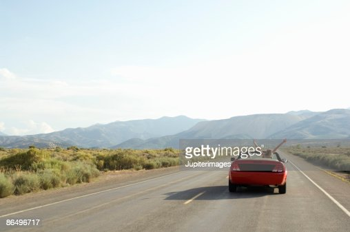 Carefree couple driving convertible on desert road