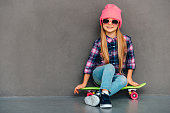 Full length of cheerful little girl in sunglasses looking at camera with smile while sitting on skateboard against grey background