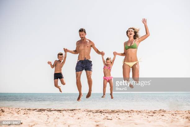 Carefree family having fun while jumping on the beach.