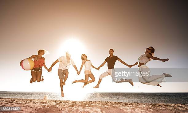 Carefree friends holding hands and jumping on the beach.