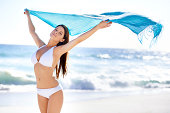 Portrait of a beautiful young woman holding a sarong that's blowing in the wind