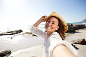 Portrait of carefree young lady on holiday at the beach taking selfie