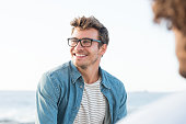 Handsome man smiling at the beach and looking away. Portrait of a cheerful guy enjoying summer vacation. Handsome man with eyeglasses in casual relaxing outdoor with friend.