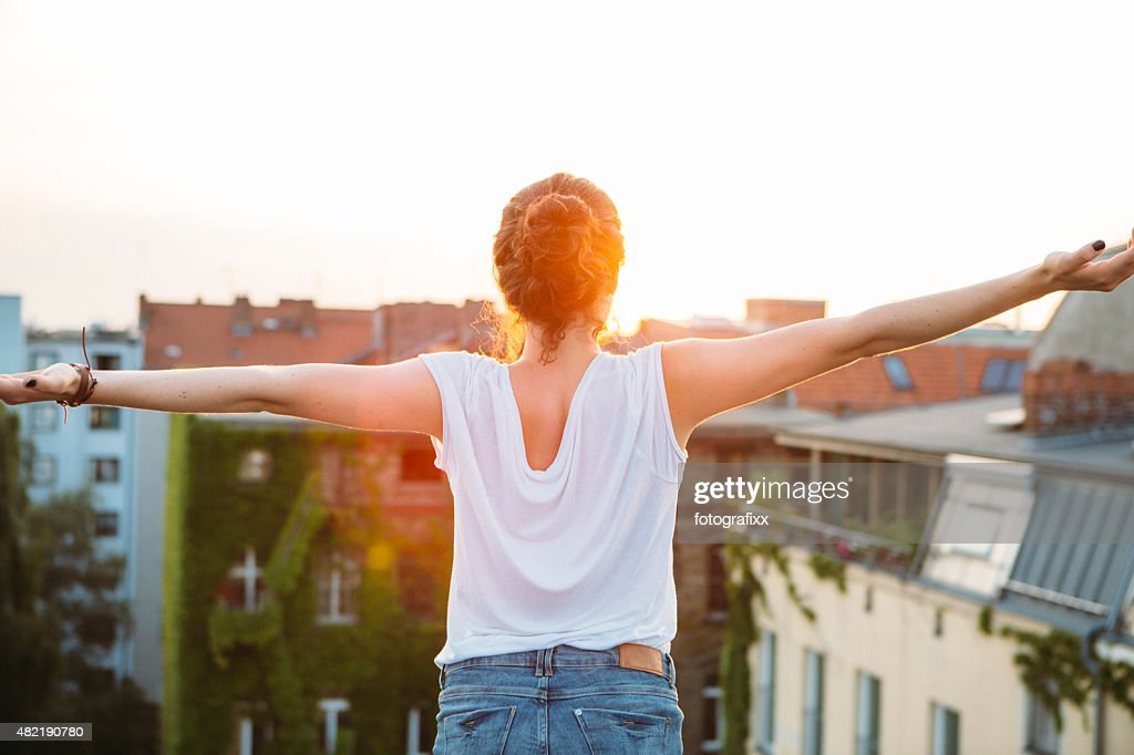 carefree summer day: rear view of young woman, feeling free