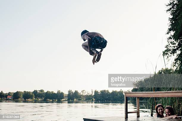 carefree summer day: teenager jumps into a lake