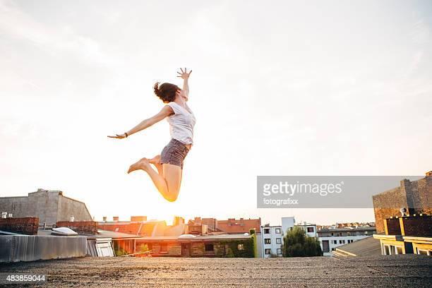 carefree été: Vue arrière de femme sautant sur un toit