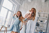 Mother and daughter holding hands and smiling while dancing in bedroom