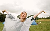 Carefree woman at campsite in poncho