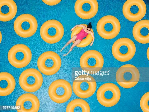 Carefree woman on ring in swimming pool