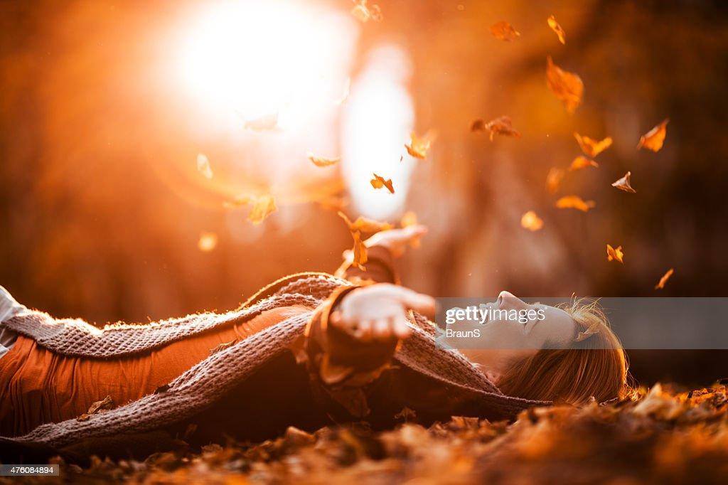 Carefree femme de détente et de lancer l'automne laisse dans la nature. : Photo