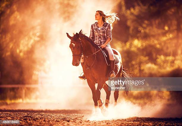 Carefree woman riding a stallion at sunset.