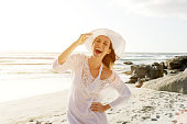 Portrait of a beautiful carefree woman walking on beach with sun dress and hat