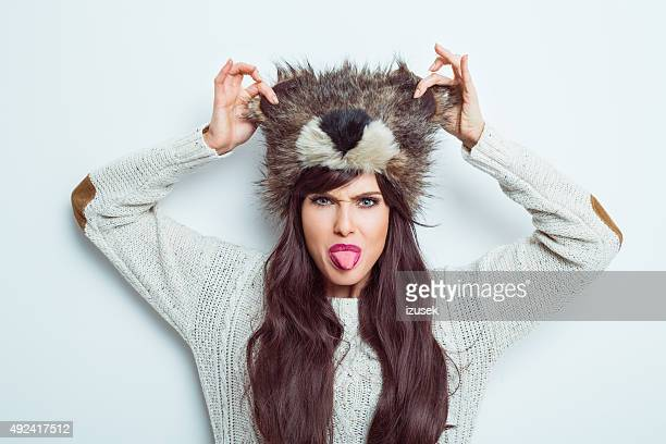 Carefree woman wearing fur cap and sticking out her tongue