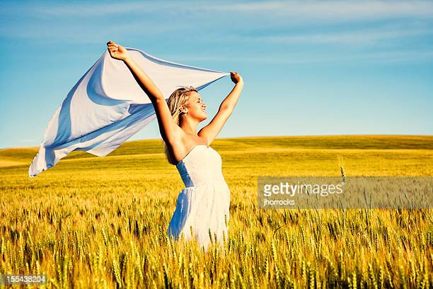 Carefree Young Woman in Golden Wheat Field